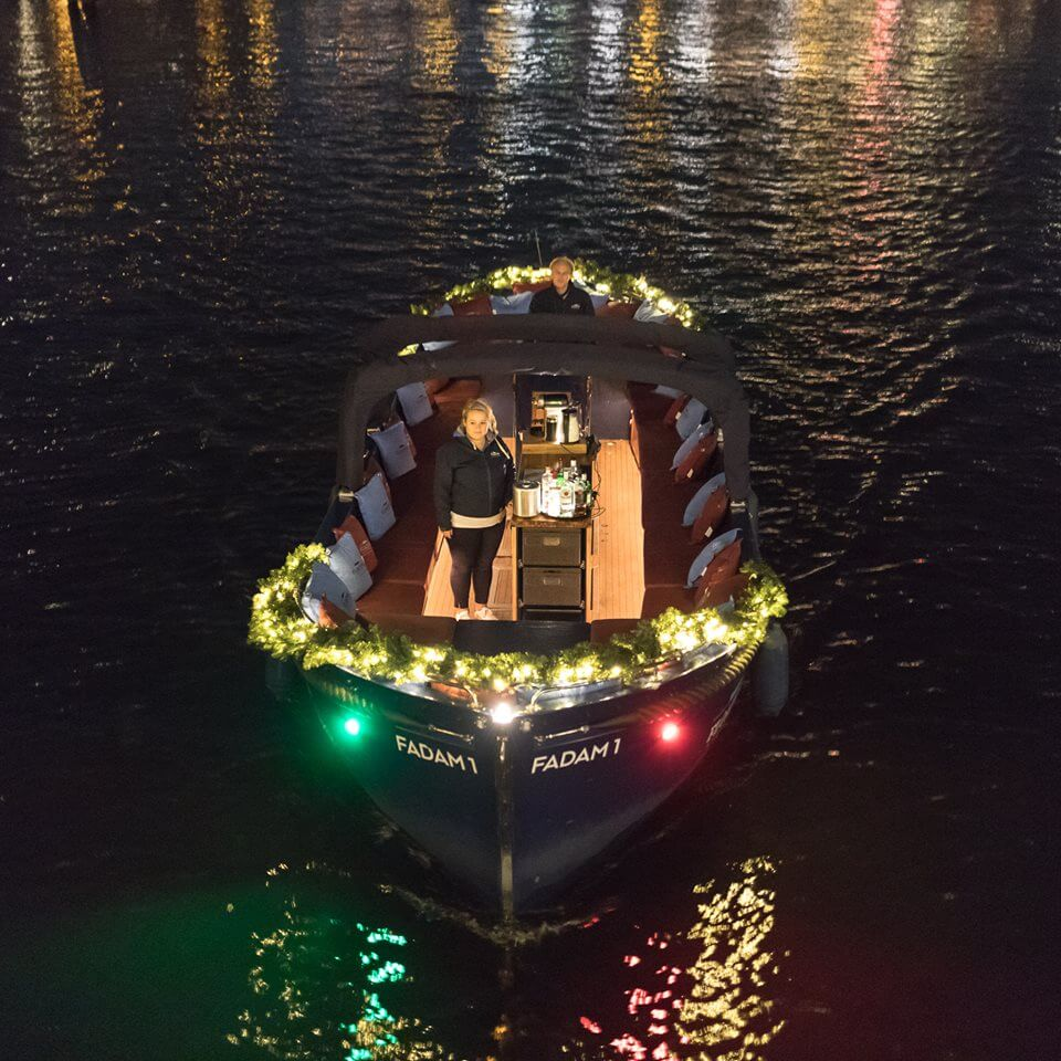 Girl on open boat during Amsterdam Light Festival canal tour