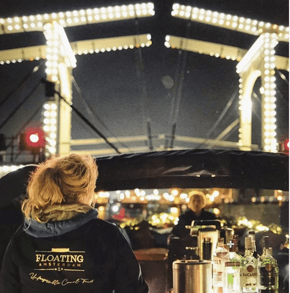 Hostess looking at Skinny Bridge during Amsterdam Light Festival canal tour